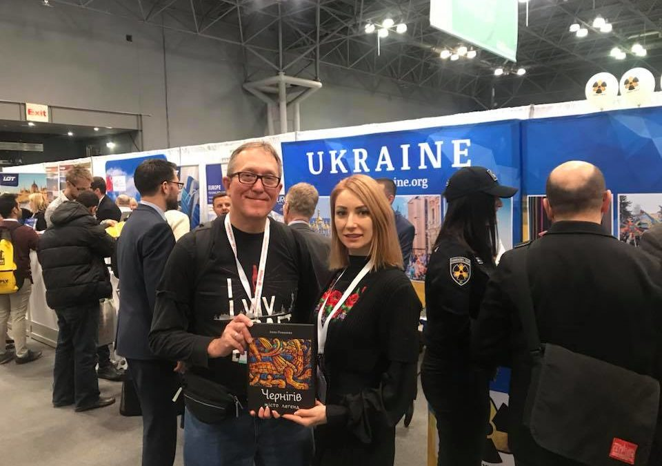 Anna Romanova, a Ukrainian Member of Parliament, presents USUF's Adrian Karmazyn with a copy of her book about Chernihiv during the New York Times Travel Show.